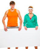 Fit girl and male athlete with blank billboard Royalty Free Stock Photo