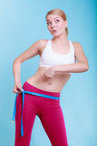 Fit girl with measure tape measuring her loins Stock Photography