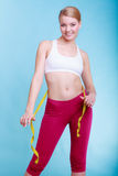 Fit girl with measure tape measuring her waist Royalty Free Stock Photos