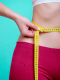 Fit girl with measure tape measuring her waist Royalty Free Stock Photo