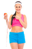 Fit girl pointing on apple with measuring tape Stock Image