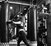 Fit girl in sportswear and boxing gloves trains. Blow against a punching bag in a dark gym. Women& x27;s self-defense training. The ability to pinch yourself stock photography