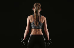 Fit girl in studio. Cross fit woman holding dumbbells standing over dark background. Concept of bodybuilding, weightlifting and training Royalty Free Stock Photos