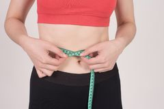 Fit girl takes her waist with a measurement tape. Beautiful young girl measuring her waist with a tape. Fit and healthy woman against soft white background Stock Photo