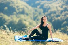 Pilates Woman Wearing Bodysuit  Overall Jumpsuit Relaxing on Yoga Mat. Fit girl taking a break to rest from exercising schedule Royalty Free Stock Photo