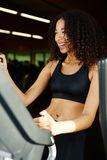 Fit girl touching treadmill screen while exercising at gym Royalty Free Stock Photos