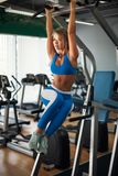 Fit girl training abs by raising legs on a horisontal bar. Fitness woman workout doing exercises at gym Stock Photography