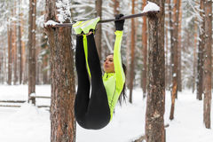 Fit girl training abs by raising legs on a horisontal bar. Fitness woman workout doing exercises outdoor winter park. Stock Images