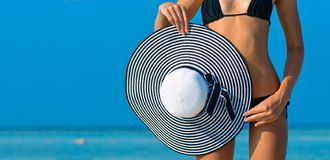 Fit girl on a tropical beach with hat. bikini body woman on paradise tropical beach. Beautiful fit body girl on royalty free stock photos