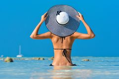 Fit girl on a tropical beach with hat. Sexy bikini body woman on paradise tropical beach. Beautiful fit body girl on. Travel vacation. Fashion photo of sexy hot stock image