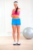 Fit girl on weight scale and measuring her waist Stock Photography