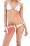 Fit girl in white bikini holding american football Royalty Free Stock Image