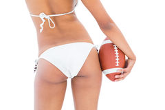 Fit girl in white bikini holding american football Stock Images