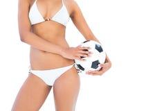 Fit girl in white bikini holding football Royalty Free Stock Photos