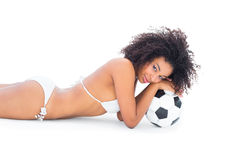 Fit girl in white bikini holding football lying on floor Royalty Free Stock Photography