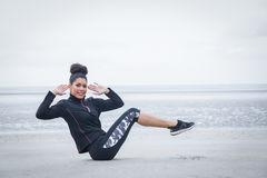 Fit girl working out on cold day. At the beach royalty free stock image