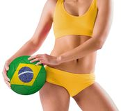 Fit girl in yellow bikini holding brazil football Stock Photo