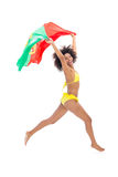 Fit girl in yellow bikini holding portugal flag laughing at camera Royalty Free Stock Photography