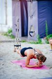 Fit girls in the gym doing exercises on the board for the spinal column and posture. Beautiful young sports people work with TRX i. N nature Royalty Free Stock Photos