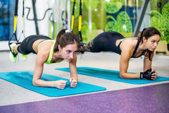 Fit girls in gym doing plank exercise for back Royalty Free Stock Photos