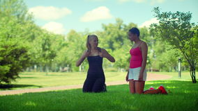 Fit girls talking kneeling on green grass in park stock video footage