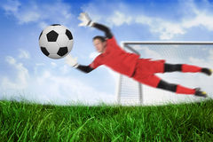 Fit goal keeper jumping up saving ball Royalty Free Stock Photos