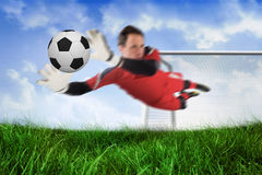 Fit goal keeper jumping up and saving ball Stock Photos