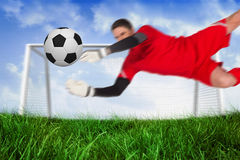 Fit goal keeper jumping up saving ball. Against field of grass under blue sky royalty free stock photo