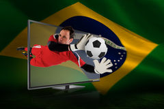 Fit goal keeper saving goal through tv Royalty Free Stock Photos