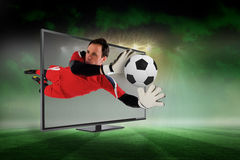 Fit goal keeper saving goal through tv. Composite image of fit goal keeper saving goal through tv against football pitch under green sky and spotlights stock image
