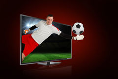 Fit goal keeper saving goal through tv Stock Photos