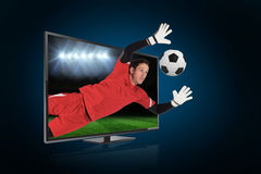 Fit goal keeper saving goal through tv Stock Photography