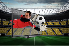 Fit goal keeper saving goal through tv. Composite image of fit goal keeper saving goal through tv against vast football stadium with fans in yellow royalty free stock image
