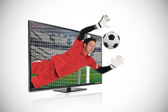 Fit goal keeper saving goal through tv. Composite image of fit goal keeper saving goal through tv against white background with vignette stock image