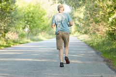 Fit grey haired mature male jogs on road, being photographed in motion, has physical exercises early in morning, wants to have hea. Lthy body, poses back to Royalty Free Stock Image
