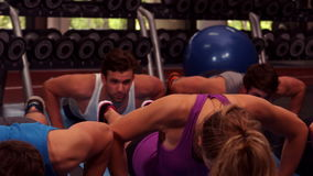 Fit group doing push ups together. In crossfit stock video