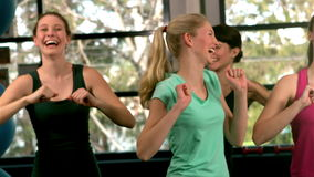 Fit group jumping and laughing in gym Stock Footage