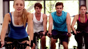Fit group of people using exercise bike together stock footage