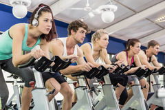 Fit group of people using exercise bike together Stock Images
