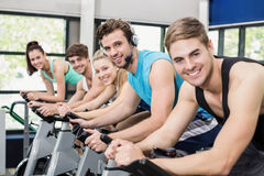 Fit group of people using exercise bike together Royalty Free Stock Photo