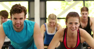 Fit group of people using exercise bike together stock video footage
