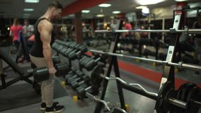 Fit guy approaching dumbbell stand and taking big fixed-weights to do exercises. Stock footage stock video