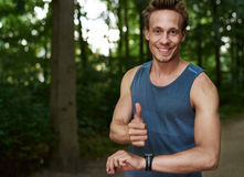 Fit Guy Showing Thumbs up at the Park. Half Body Shot of a Smiling Fit Guy at the Park Showing Thumbs up and a Hand with Wrist Watch at the Camera Stock Images