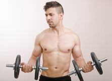 Fit guy. Young man lifting weights in studio background Royalty Free Stock Photos