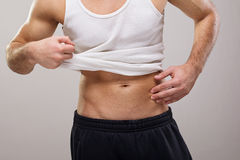 Fit handsome guy in white shirt showing his abs Royalty Free Stock Photo