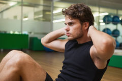 Fit handsome man doing sit ups in fitness studio Royalty Free Stock Photography