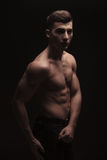 Fit handsome man side posing in dark studio background while fle Stock Photography