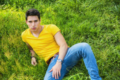 Fit handsome young man relaxing lying on lawn Royalty Free Stock Image