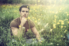 Fit handsome young man relaxing lying on lawn. Attractive, fit young man relaxing sitting on lawn in the countryside among grass, looking at camera, smiling Stock Image