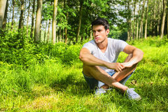 Fit handsome young man relaxing lying on lawn Stock Photo